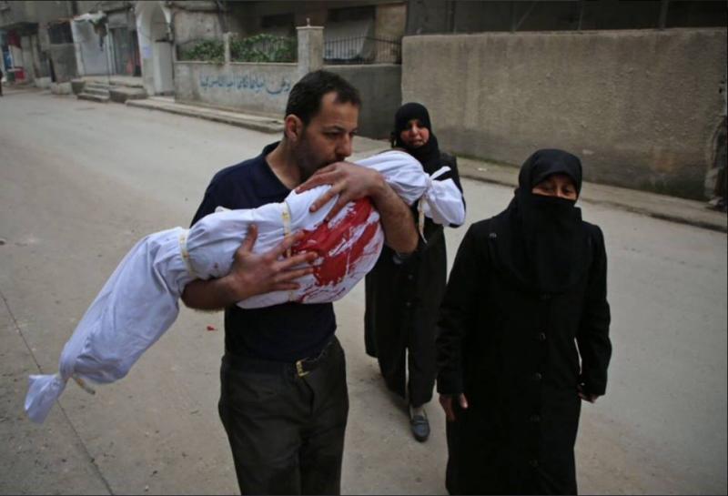 Siria, mormântul copilăriei. Imaginea care-ți taie respirația: Un tată își cară copilul mort, într-un cearșaf. Nu merg acasă, ci la groapă