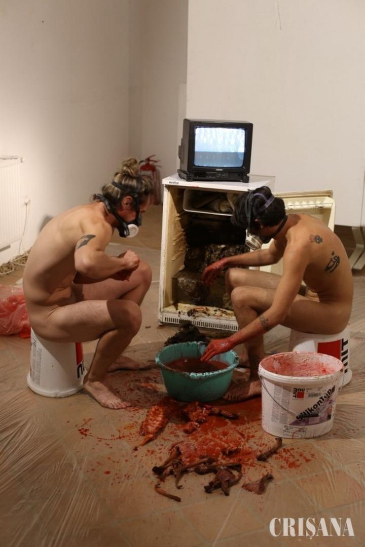 FOTO/ Galerie de artă sau scene dintr-un film de groază? Doi tineri artiști eu prezentat, dezbrăcați complet, scene macabre la o expoziție din Oradea