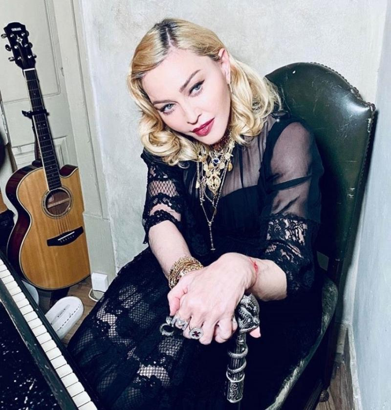 Madonna este așezată pe scaun, cu o chitară lângă ea