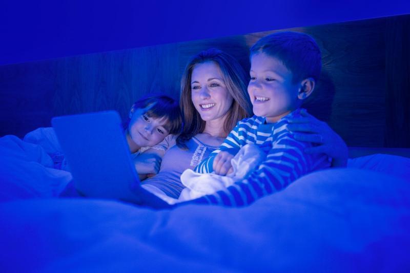 mama cu doi copii in pat uitandu-se la laptop pe intuneric