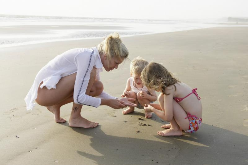 mama cu doi copii la plaja culegand scoici