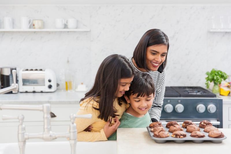mama cu doi copii facand fursecuri in bucatarie