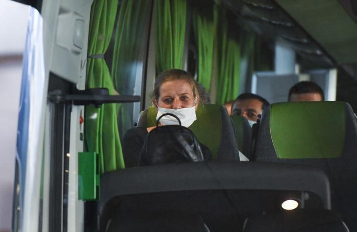 Muncitori români fac cu mâna dintr-un autocar