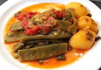 Cartofi cu păstăi de fasole în sos de roșii cu usturoi. O mâncare de vară rapidă și gustoasă.
